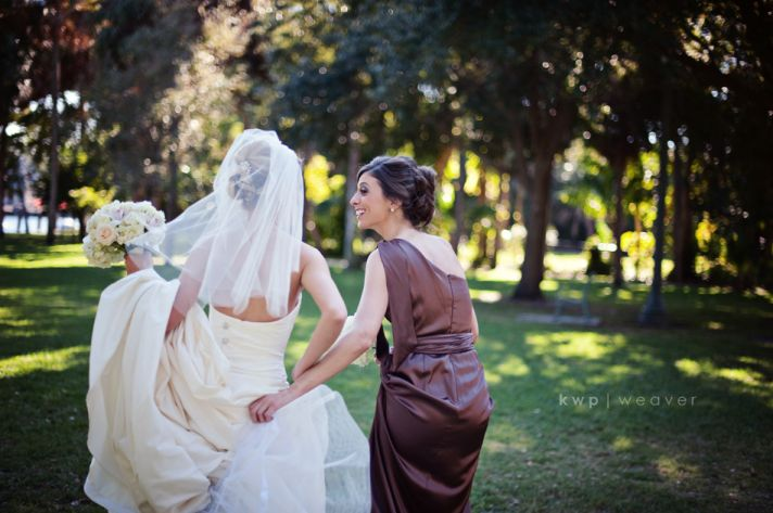 Bridesmaid wears mocha one-shoulder bridesmaid dress, helps bride with train