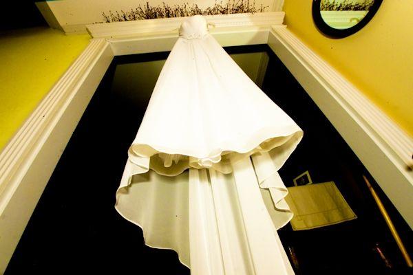 Ivory ballgown wedding dress hangs in door of wedding ceremony venue