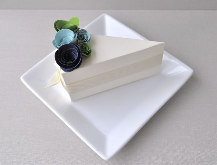 Chic ivory wedding guest favor boxes shaped like a slice of wedding cake, adorned with blue and gree