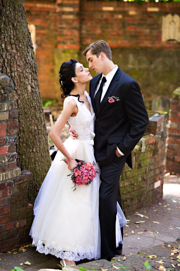 Bride in vintage wedding dress poses with groom