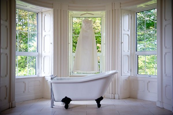 Ivory wedding dress hangs in window of wedding venue