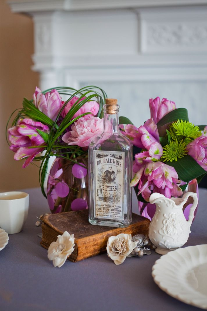 Wedding reception centerpieces of pink peonies with vintage bottles and other table details