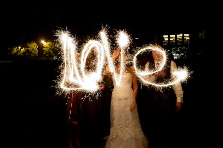 Bride and groom spell LOVE with sparklers at wedding reception