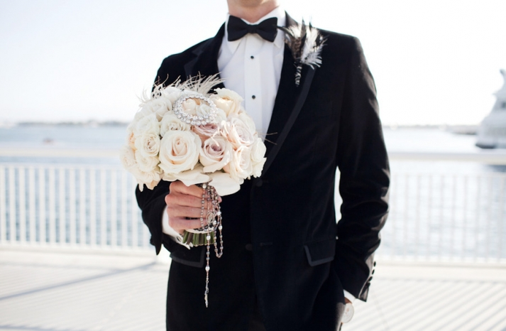 black tie groom holds brides elegant bridal bouquet