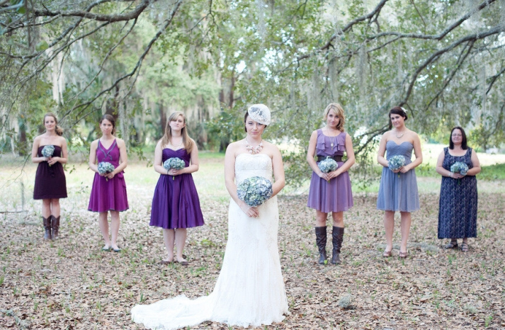 bride poses with mix and match bridesmaids some in cowboy boots