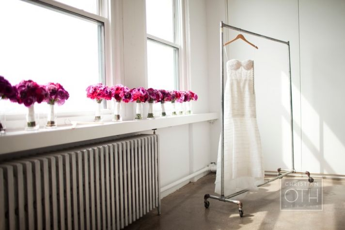 monique lhuillier wedding dress hangs with flower girl dresses