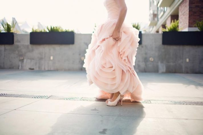 bride wears pink vera wang wedding dress shows off wedding shoes