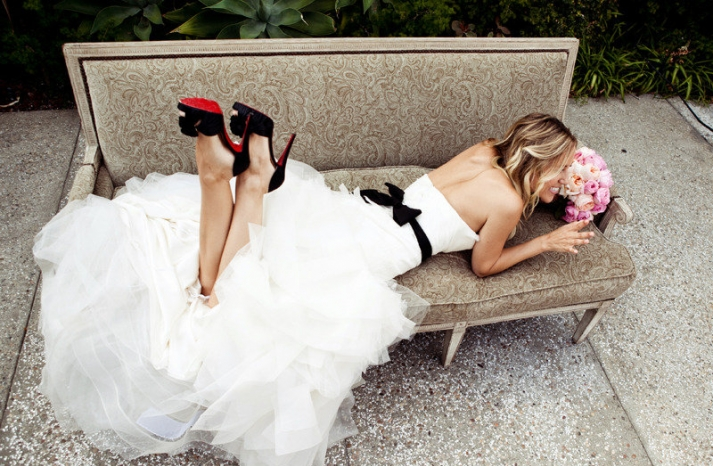 bride wears white wedding dress with black sash