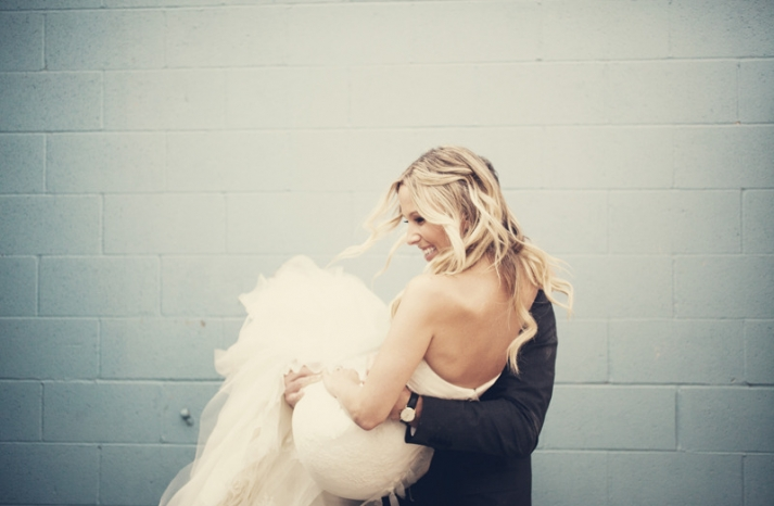 groom carries bride over threshold