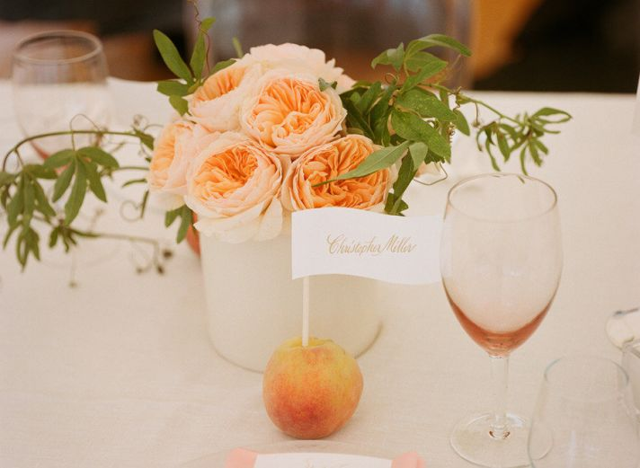 fruit incorporated into wedding reception centerpieces peaches hold escort cards