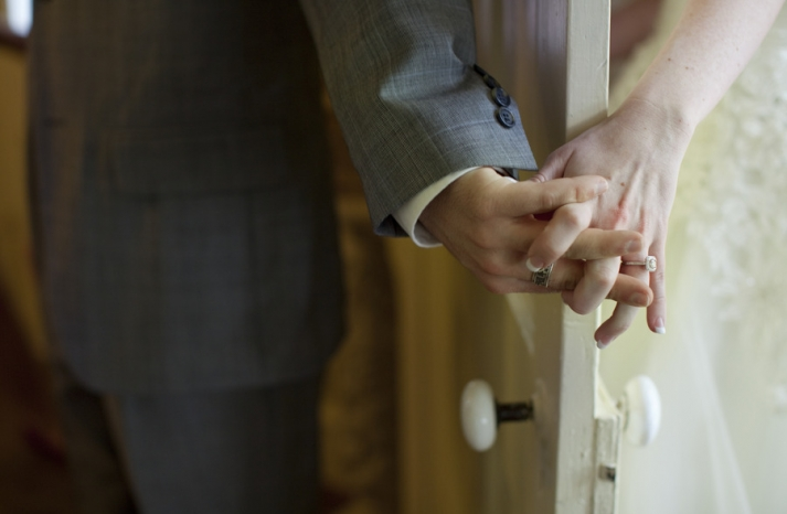 first look artistic wedding photo bride groom hold hands
