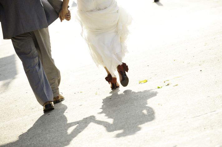 Bride and groom walk hand in hand to wedding reception