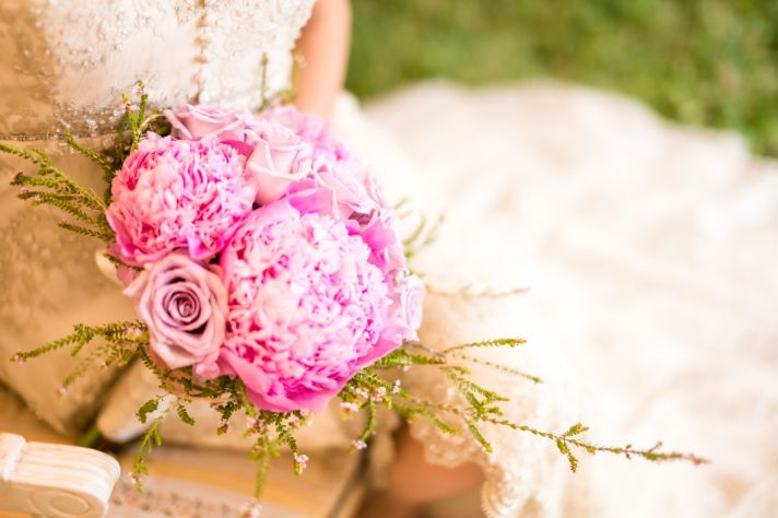 Vintage bride hides behind fluffy peony bouquet