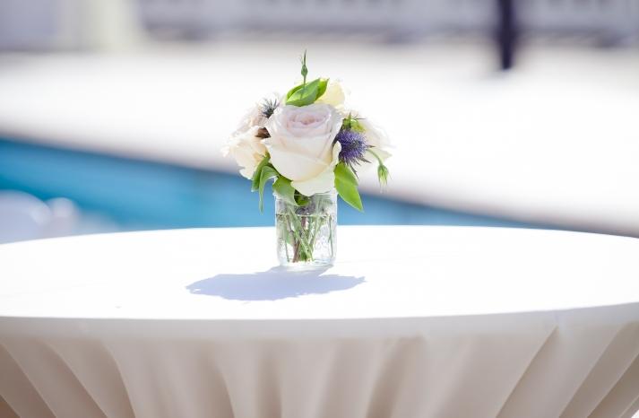 Simple wedding centerpiece atop highboy table