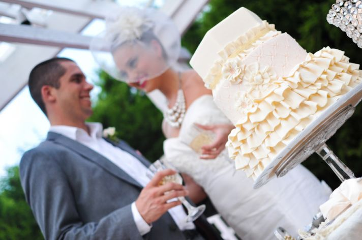Bride and groom prepare to cut wedding cake