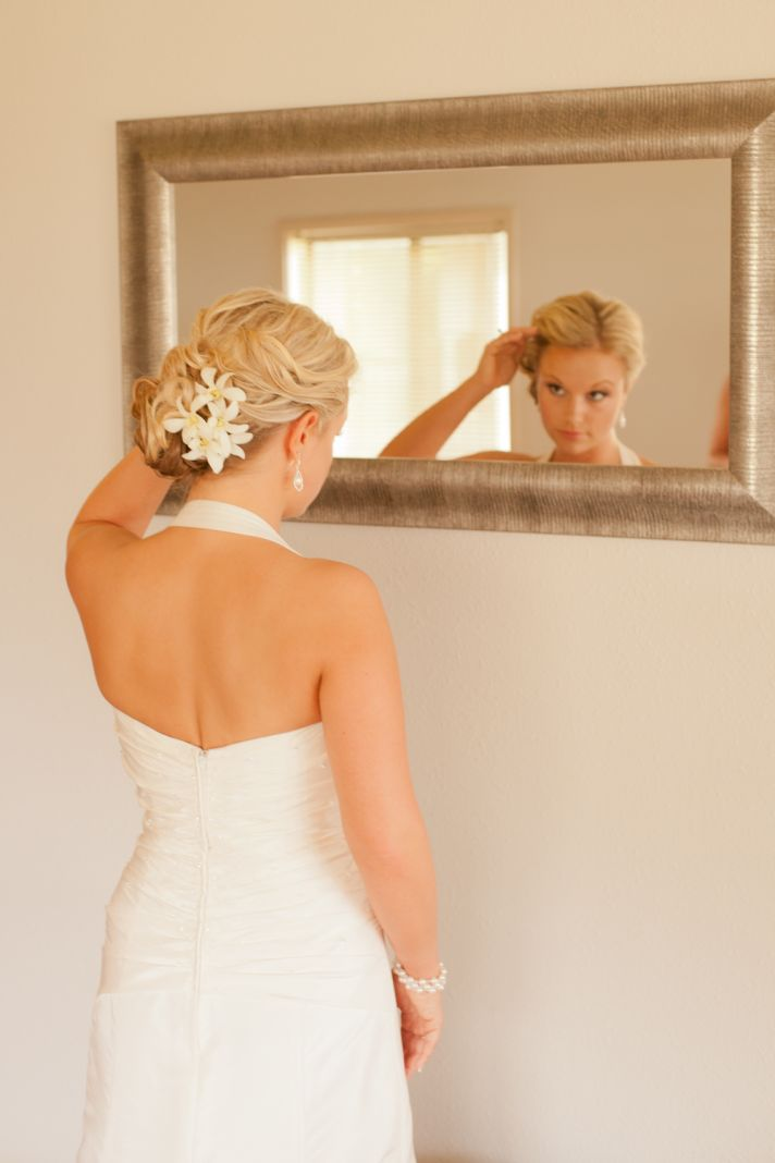 Destination wedding bridal updo finished with ivory blooms