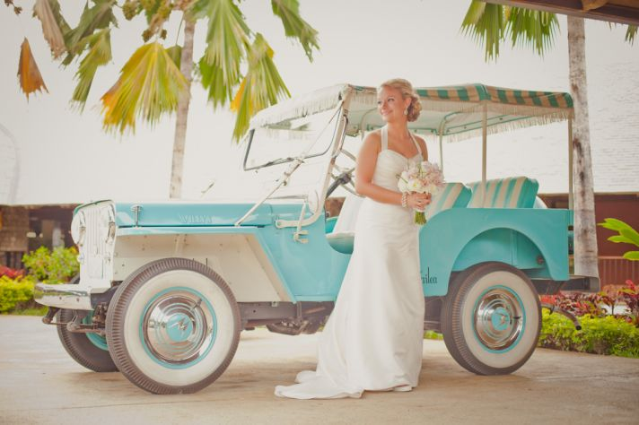 Destination bride poses in front of awesome aqua rickshaw