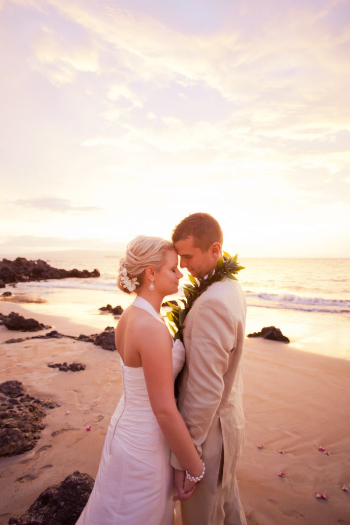 bride and groom hold wedding bands atop sand
