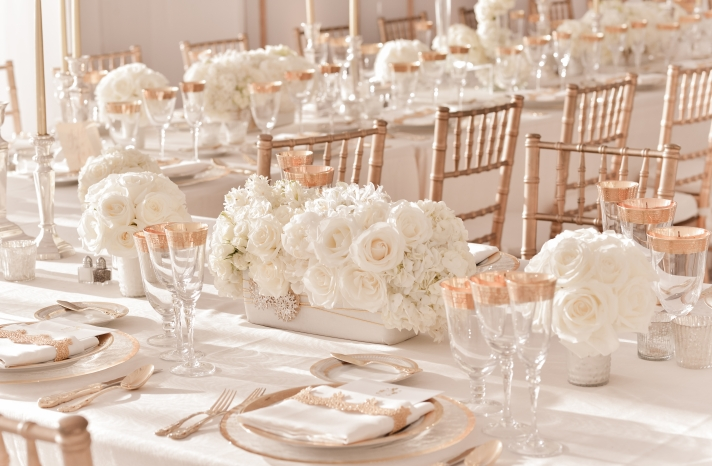 elegant ivory wedding centerpieces with rose gold table accents and chairs