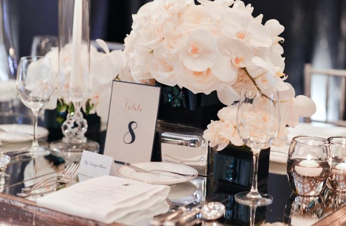 White orchids in emerald vases at elegant wedding reception