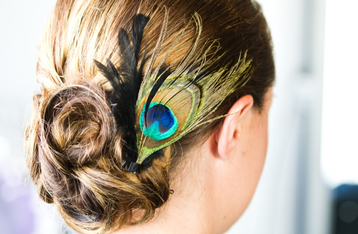 bridesmaids updo finished with a peacock feather fascinator