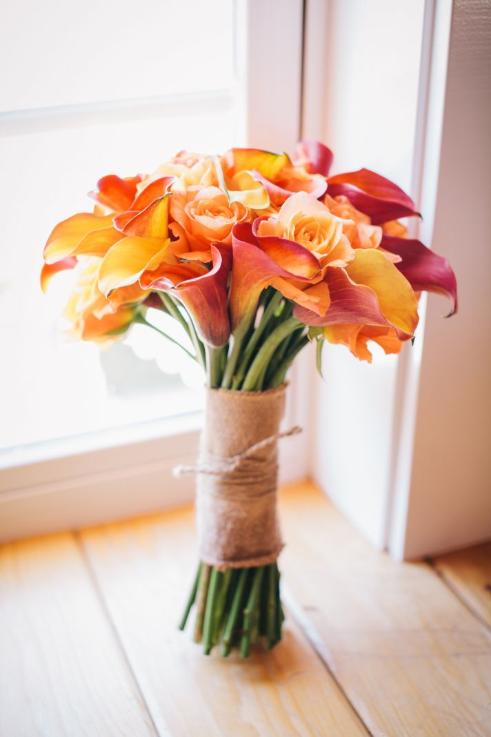 orange and yellow wedding bouquet wrapped with burlap