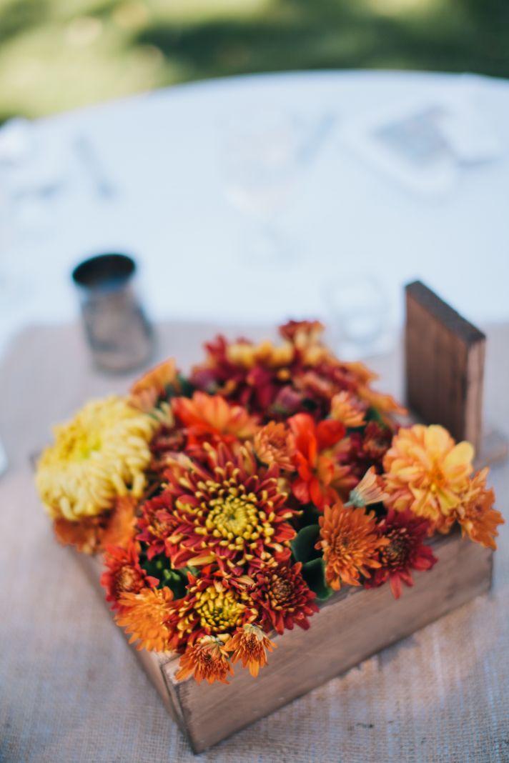 Rich fall wedding centerpiece arranged in wood planter