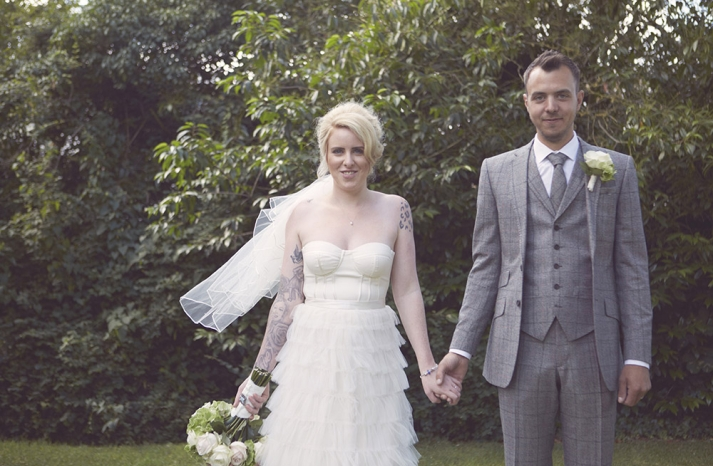 groom poses with bride in 3 piece charcoal gray patterned suit