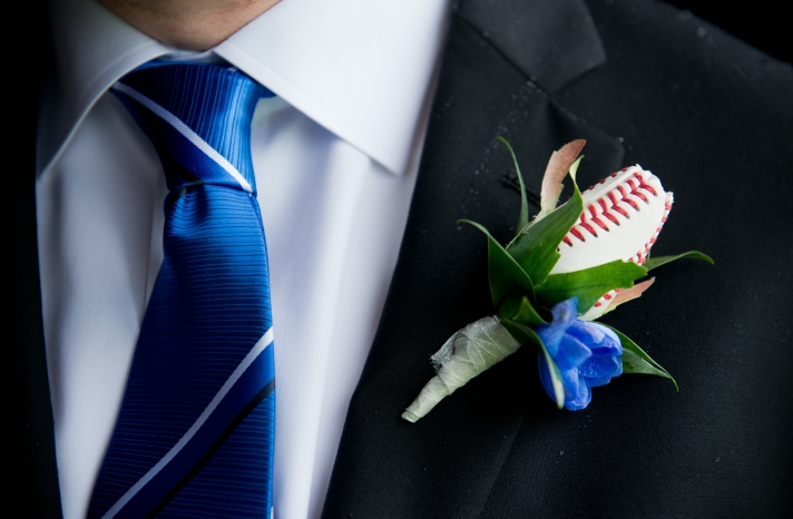 groom wears blue tie with baseball boutonniere