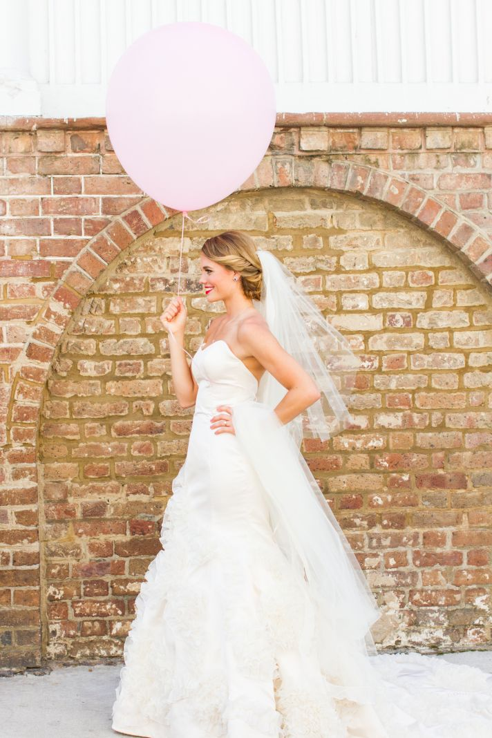 Classic beautiful bride poses with pale pink balloon