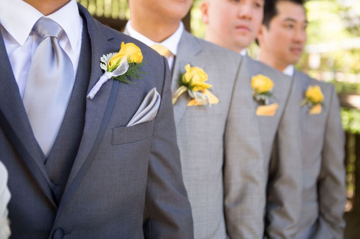 Yellow boutonnierres and grey groomsmen suits