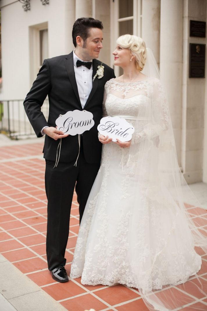 Vintage bride and groom pose with signs